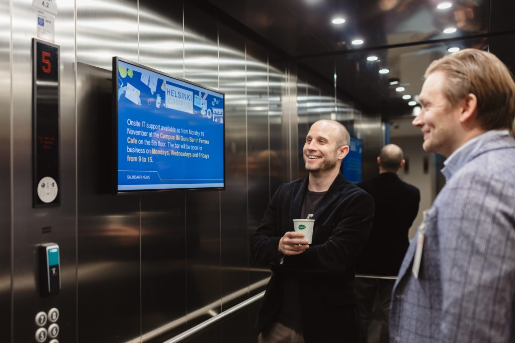 Men looking at workplace Info Screen in elevator